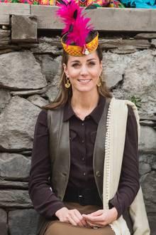Dazu trägt die Herzogin auffällige goldene Ohrringe von Missoma für rund 130 Euro. Traditioneller Kopfschmuck mit pinken Federn setzt einen farbigen Akzent zu den sonst gedeckten Tönen.
