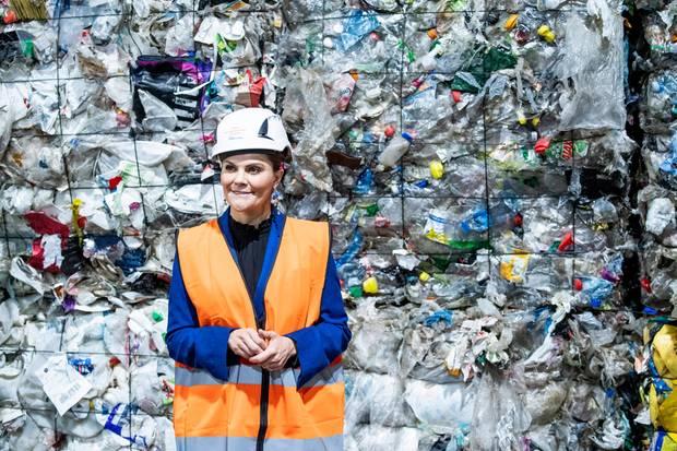 Mit Sicherheitshelm und Warnweste bekleidet steht Prinzessin Victoria beim Besuch von Europas größter Recyclinganlage vor einer Wand aus Plastikmüll.