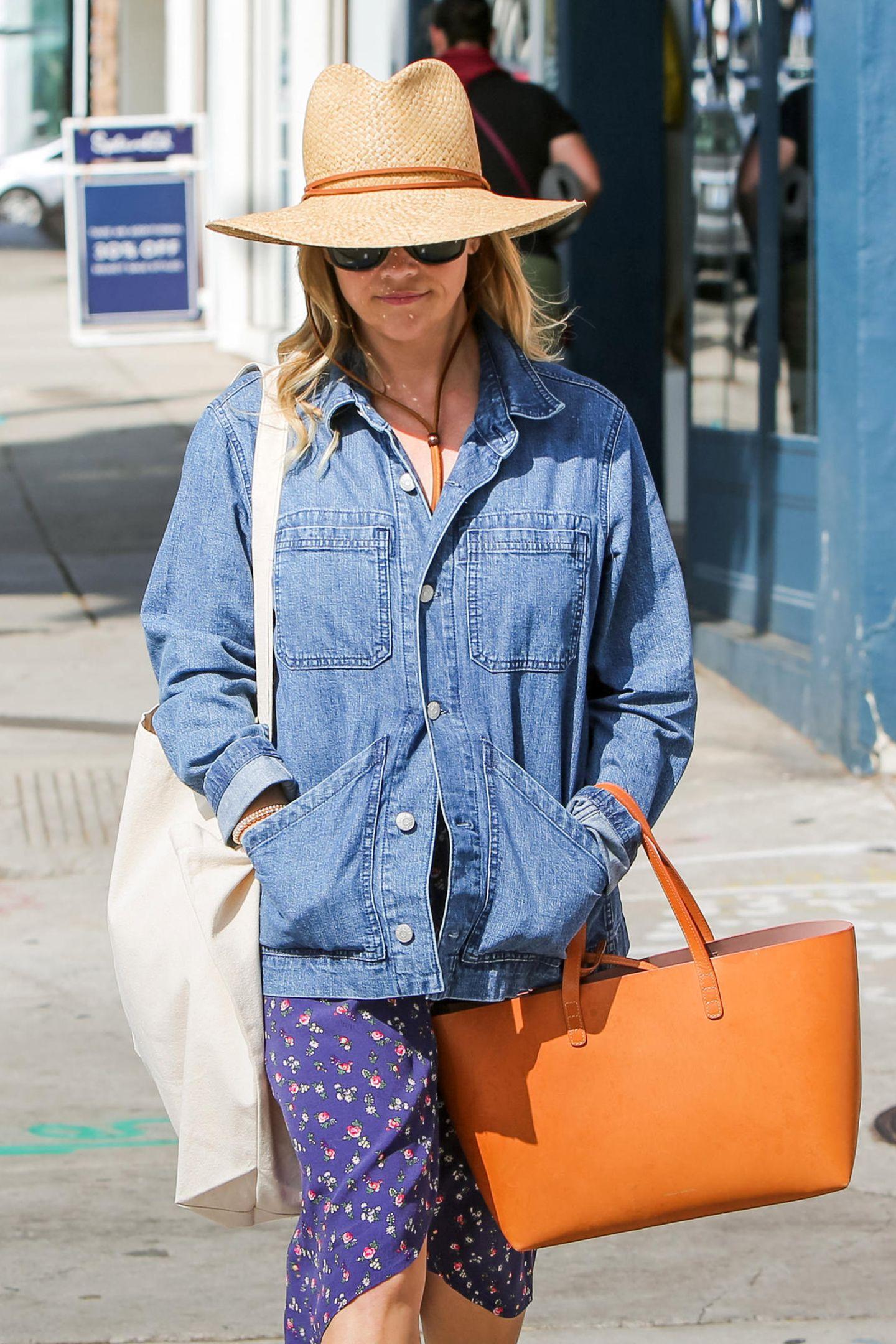 Mit Sonnenhut und Blümchenkleid. Dieser Look von Reese Witherspoon schreit förmlich nach Ausflug zum Bauernmarkt. Passend dazu trägt die Big Little Lies Schauspielerin ihre Mansur Gavriel Tote im sonnigen Camel Farbton.