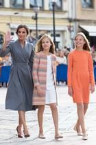 """Bei den """"Princesa de Asturias""""-Awards 2019 hältsich Königin Letizia elegant zurück: Sie trägt ein graues Blazerkleid und dazu weinrote Pumps. Ihre Töchter Leonor und Sofía dagegen strahlen in der Trendfarbe Orange und haben sich mit Mantel und Kleid perfekt aufeinander abgestimmt."""