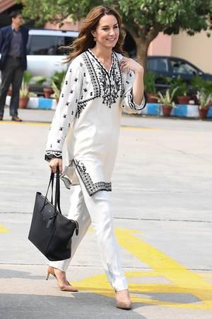 Für den Rückflug nach Islamabad zeigt sich Catherine in einem Ersatz-Outfit. Der Flieger, der sie und William am Vorabend zurückbringen sollte musste außerplanmäßig zurückfliegen. Nach Substitut sieht ihre schwarz-weiße Kurta von Élan jedoch nicht aus. Dazu kombiniert sie beige Pumps von J.Crew und eine weiße Hose.