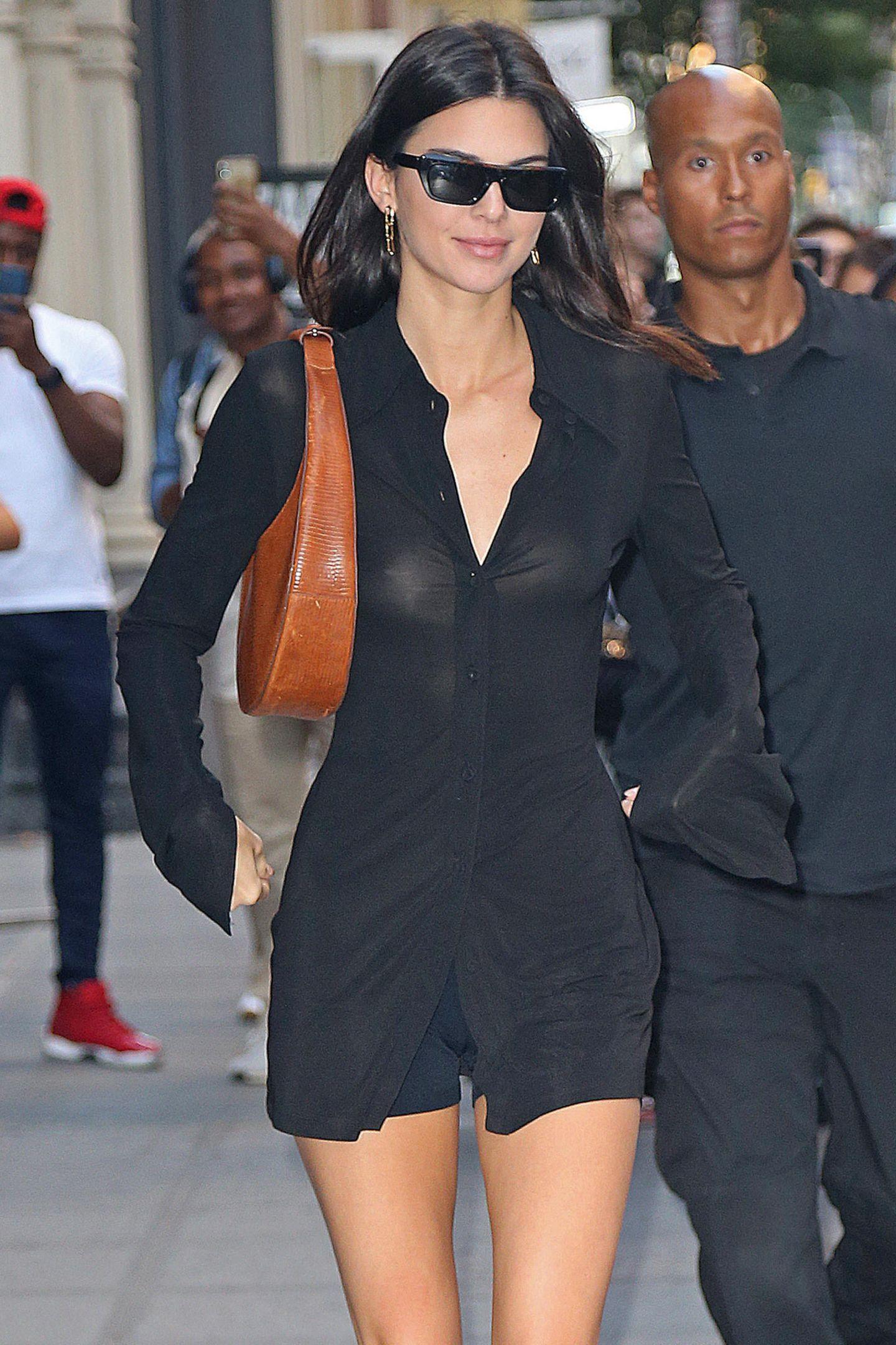 """Der Mond, der treue Begleiter bei Nacht – bei Kendall Jenner sogar den ganzen Tag. Als lässiges It-Piece trägt sie ihre """"Large Moon Bag"""" von Staud um die Schulter. Sie ist aber auch ein wahrer Hingucker, insbesondere zum schwarzen Blusenkleid und High-Boots."""