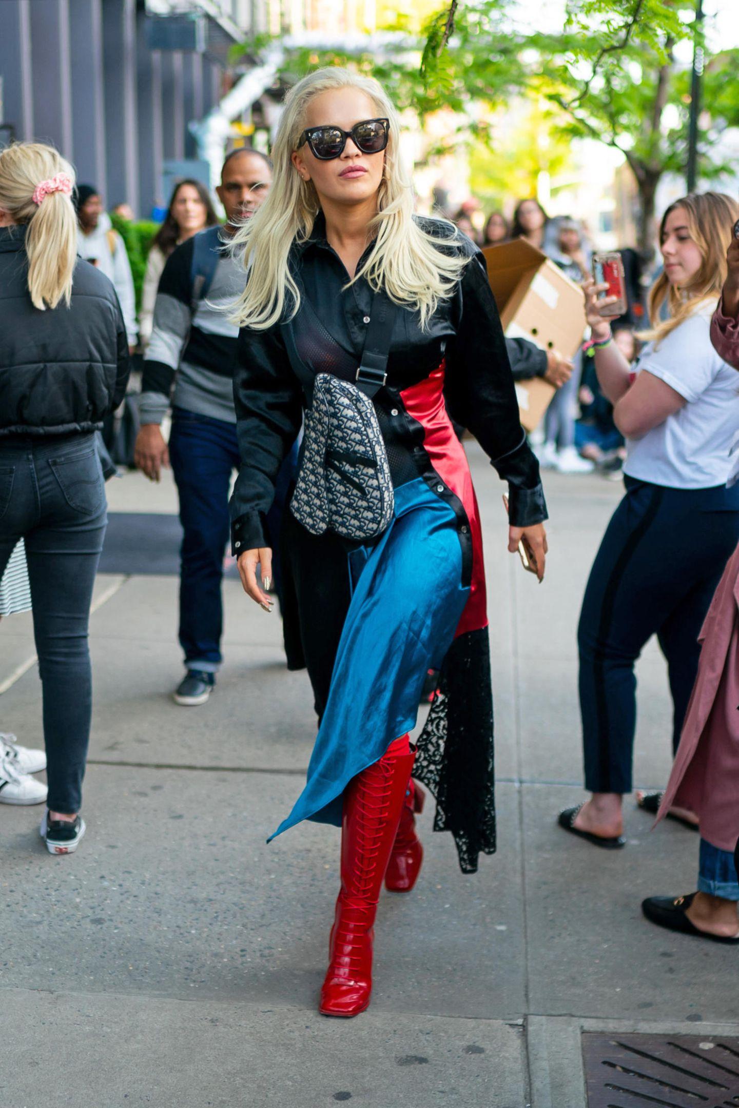 """Ursprünglich 1999 von John Galliano für Diordesignt, findet die """"Saddle Bag""""in der Herbst/Winter Saison2018, dankMaria Grazia Chiuri ihr ultimatives Comeback. Seitdem ist die ikonische Tasche aus demModeolymp nicht mehr wegzudenken und ziert das ein oder andere Promi-Handgelenk. Rita Ora entscheidet sich hier gegen den klassischen Schulterriemen und trägt ihre """"Saddle Bag"""" im Crossbody-Style."""