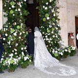 Der langeSchleier der Gräfin ist wie das Kleid selbst mit blätterförmiger Spitze verziert. So schreitet die Gräfin durch dieoppulent blumenverzierte Kirchentür.