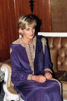 Prinzessin Diana trägt bei ihrem Besuch in Pakistan eine violette Variante des traditionellen Gewands. Die Stickereien sind in edlem Gold gehalten.