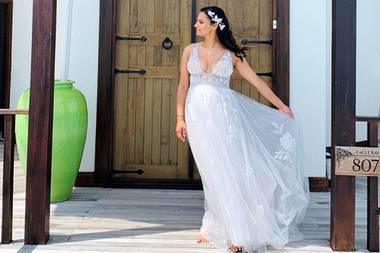 Amira Aly trägt ein bodenlanges, weißes Brautkleid. Der Rock des Kleides besteht aus einem langen Unterrock und einer mit Blüten bestickten Tüllschicht. Das Blütenmuster findet sich auch im oberen Bereich des Kleides wieder. Das ärmellose Hochzeitskleid, transparente Elementeund ein extrem tiefer Ausschnitt setzen Amiras Dekolleté in Szene. Auch der Babybauch der werdenden Mutter wird stilvoll betont.