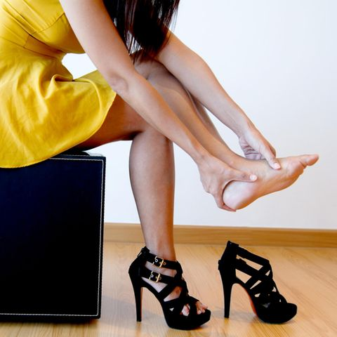 Frau zieht ihre High Heels aus