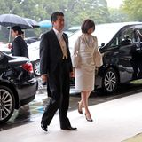 Japans Premierminster Shinzo Abe und seiner Ehefrau Akie erreichen bei strömendem Regen den Kaiserpalast.