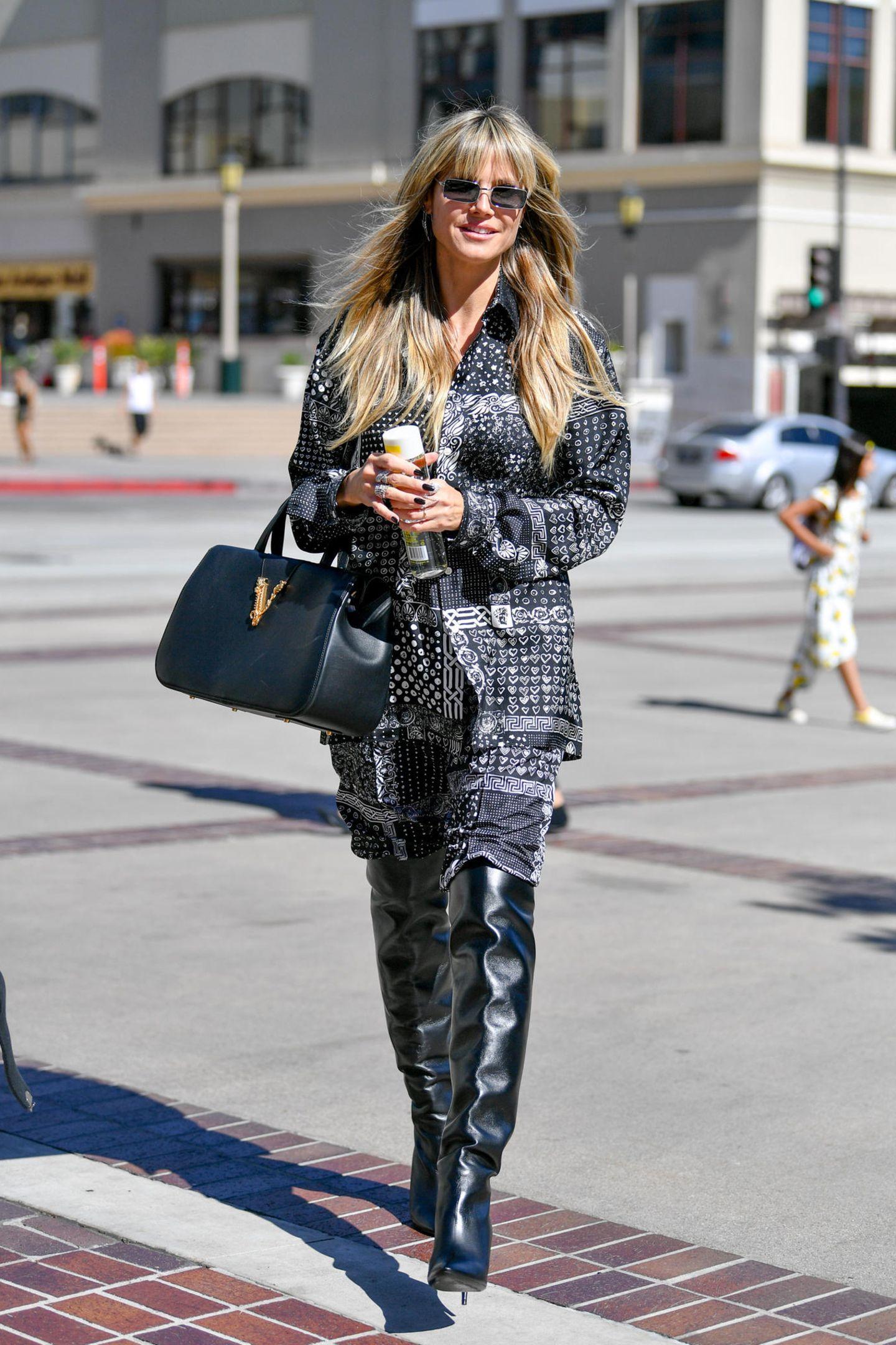 Wozu sich unnötig vieleGedanken um das Tagesoutfit machen, wenn man doch gleich seinen Pyjama anlassen kann. Das denkt sich offenbar auch Heidi Klum, die durch Los Angeles in einem Designer-Zweiteiler spaziert. Die langen Hosenbeine stecken in sexy Overknees, das XL-Shirt hängt lässig über der Hose. Ein Pyjama, der hier als Style-Element und weniger als Schlafutensil genutzt wird.