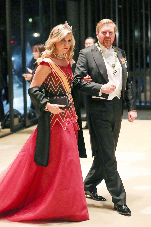 Auch Königin Máxima hat eine optische Verwandlung hingelegt: Morgens noch mit Hut, zarten Tönen und geschlossenen Haaren, setzt sie jetzt auf ein rotfarbenes Hingucker-Kleid mit offenen Haaren und royalen Schmuckstücken.