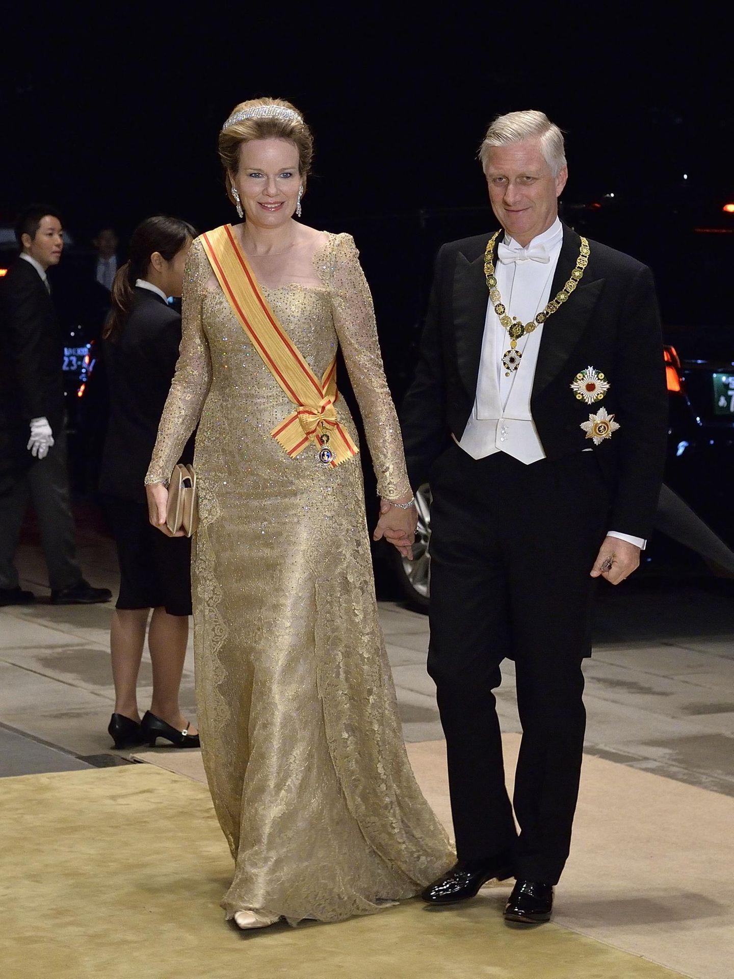 Auch Königin Mathilde setzt für den Abend auf Glitzer und erscheint in einer bodenlangen Robe mit einer Schleppe aus goldener Spitze und einem durchsichtigen Einsatz am Dekolleté. Während sich die Schärpe farblich absetzt, passen Schuhe und Clutch perfekt zum Kleid. Die opulenten Schmuckstücke sorgen für noch mehr Glamour.