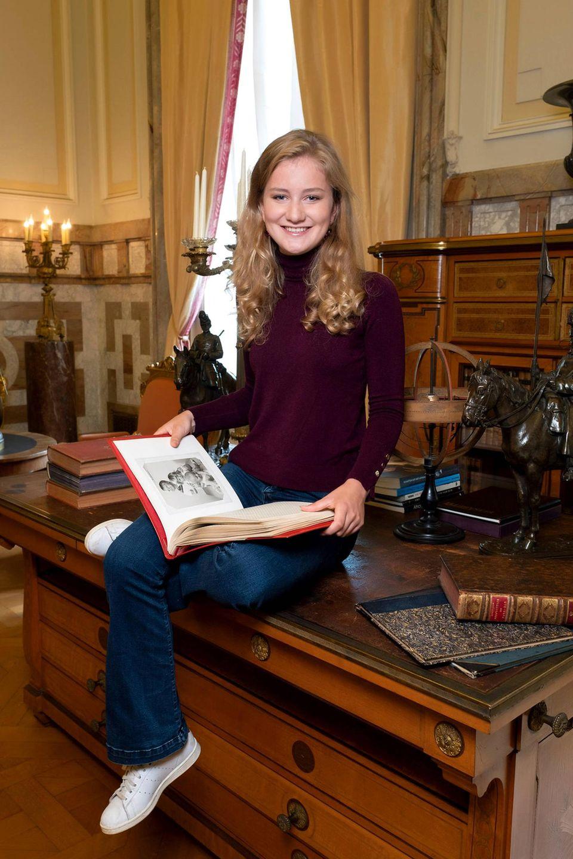 23. Oktober 2019  Fröhlich lächelt die belgische Kronprinzessin beim Betrachten eines Familienalbums in die Kamera des Fotografen.