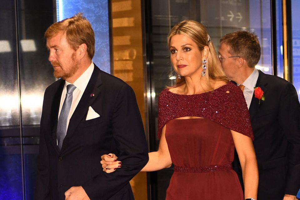 Den bordeauxroten Overall von Königin Máxima der Niederlande ziert ein funkelndes Mini-Cape, das dem ansonsten sehr schlichten Design seine besondere Eleganz verleiht.