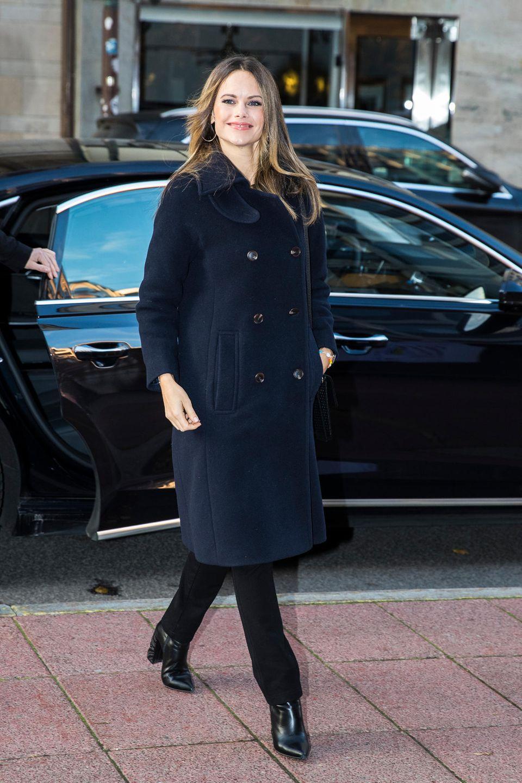Prinzessin Sofia von Schweden erscheint strahlend zu einer Konferenz in Stockholm. Sie trägt einen dunkelblauen Mantel mit doppelreihiger Knopfleiste und eine dunkle Hose. Silberne Creolen machen ihren stylischen Look perfekt. Besonderer Hingucker sind jedoch ihre coolen spitzzulaufenden Boots mit hohem Blockabsatz.