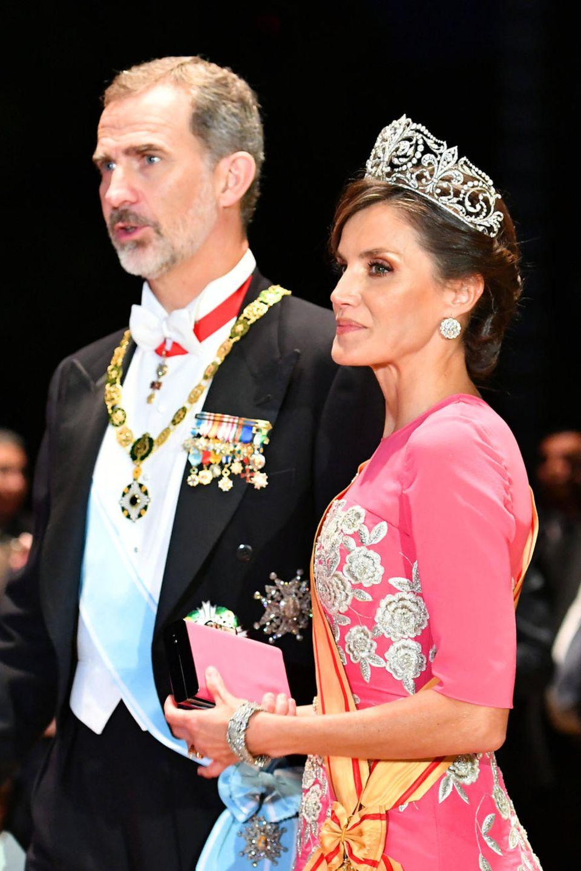 """Königin Letizia von Spanien erscheint zur Krönung des Kaisers von Japan mit einem auffällig fuchsiafarbenen Kleid, das alle Blicke auf sich zog. Aber auch ihrhochkarätiges Diademmit dem Namen """"Fleur de Lys"""" gilt als eines derschönsten der spanischen Königsjuwelen und trägt den Spitznamen """"La Buena"""" oder """"das Gute"""".Das eindrucksvolle Diadem besteht aus Platin, das mit mehr als 500 einzelnen Diamanten besetzt ist. Es zeigt das Wahrzeichen der Familie von König Alfonso."""