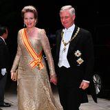 Königin Mathilde glänzt in Gold und hält mit ihrem Mann König Philippe Händchen.