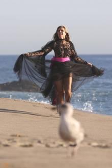 """Für die neue Staffel von """"Germany's next Topmodel"""" hat sich die Model-Mama in ein gewagtes Outfit geworfen: In einem schwarzen, transparentem Tüllkleid, hüpft die46-Jährige gut gelaunt am Strand von Malibu entlang, um uns dann..."""