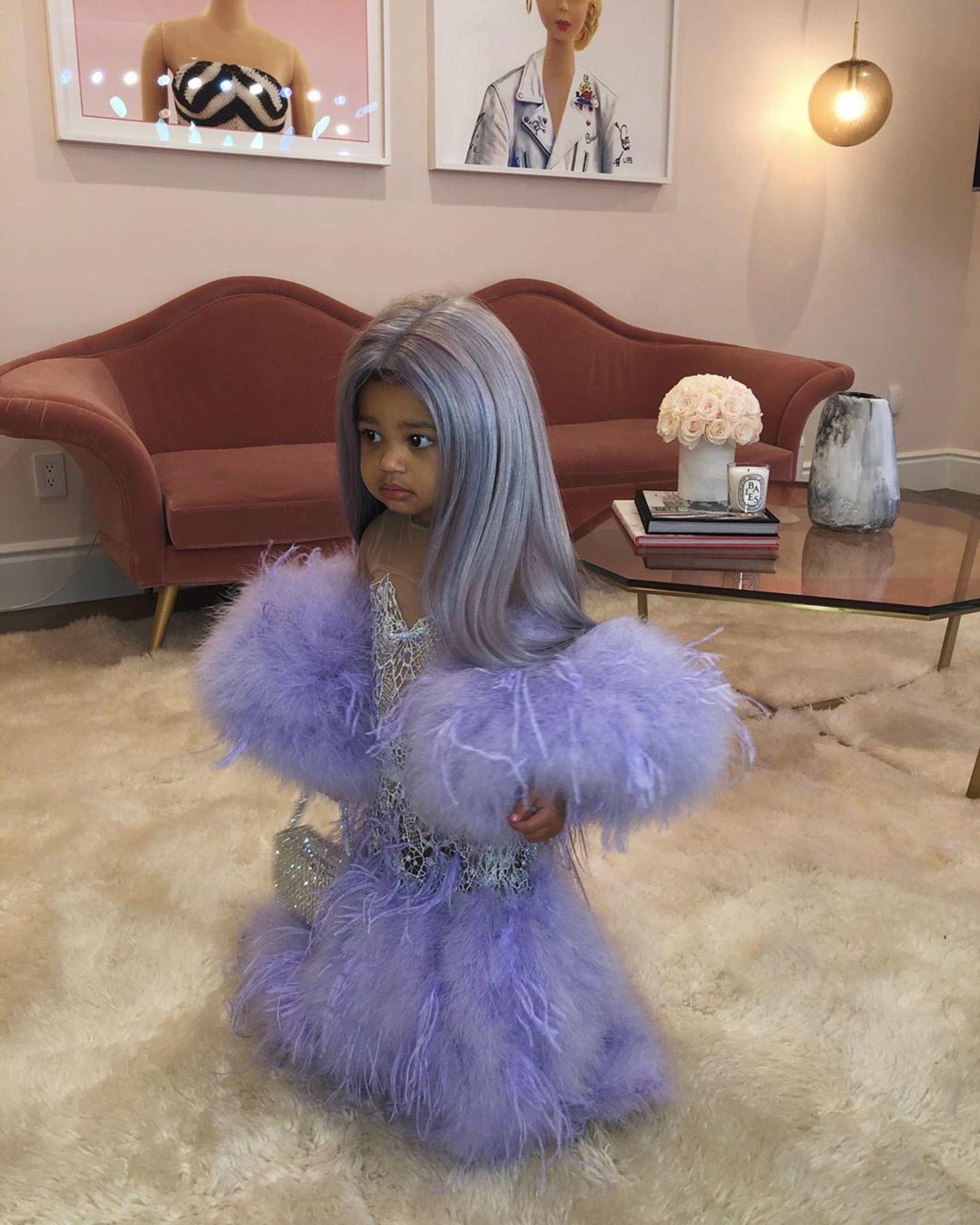 Ob Stormi bereits wenige Tage vor Halloween ihr Kostüm anprobieren darf? Mit einer lilafarbigen Perücke und farblich passendem Glitzer-Kleid mit Feder-Applikationen an Arm und Saum ist die einjährige Tochter von Kylie Jenner kaum wiederzuerkennen. Ihr selbst scheint das ganze Kostüm auch nicht so richtig geheuer - oder sie übt schon einmal ihr gruseliges Halloween-Face.