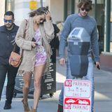 """Alessandra Ambrosio flaniert durch Santa Monica im sytlischenBoho-Outfit. Ein kurzer Jumpsuit im floralen Print wird zur Fransenjacke und Cowboy-Boots kombiniert. Perfekt abgerundetwird der Look vonder """"Gate""""-Bag von Loewe."""