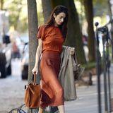 """Die Farben des Herbsts stehen Amal Clooney ausgezeichnet! Die Juristin trägt einen Look in verschiedenen rostroten Nuancen, als sie im herbstlichen New York gesichtet wird. Ihre hochgeschlossene, kurzärmelige Bluse hat sie lässig in ihren taillenhohen Midi-Rock gesteckt, der für eine schöne Silhouette sorgt. Dazu passend trägt Amal eine braune Wildleder-Tasche in der einen und einen kamelfarbenen Trenchcoat in der anderen Hand. Ein besonderer Hingucker sind die Schuhe der zweifachen Mutter: Denn sie trägt die Jimmy Choo """"Fetto"""" Pumpsim angesagten Schlangen-Print für rund 695 Euro."""
