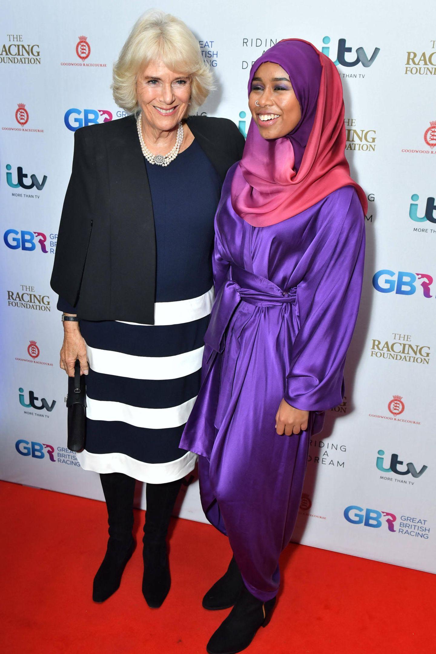 """28. Oktober 2019  Bei der Premiere des Filmes """"Riding A Dream"""" posiert Herzogin Camilla mit Hauptdarstellerin Khadijah Mellah, dem ersten Jockey, der in Großbritannien mit einemHidschabbekleidet ein Pferderennen antrat - und gewann."""