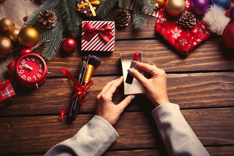 Beauty-Adventskalender, Frau nimmt Lippenstift aus kleiner Schachtel, kleine Geschenke um sie herum