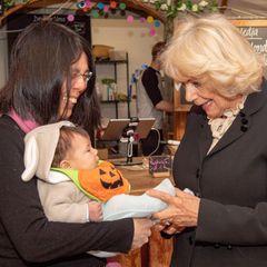 """Bei ihrem Besuchdes """"Yurt Cafe"""", einem Sozialunternehmen der Stiftung """"The Royal Foundation of St. Katharine""""in London, findet Herzogin Camilla diesen kleinen Kürbis einfach zum Anbeißen. Die Sympathie beruht auf Gegenseitigkeit, denn das Baby kichert beim Anblick der Herzogin fröhlich vor sich hin."""
