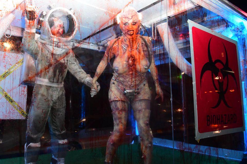 """Tom Kaulitz und Heidi Klum kommen Hand in Hand bei Heidis Halloween-Party an. Der """"Tokio Hotel""""-Star ist als blutüberströmter Forscher verkleidet, das Model als menschliches Laborexperiment, so sieht es zumindest aus."""