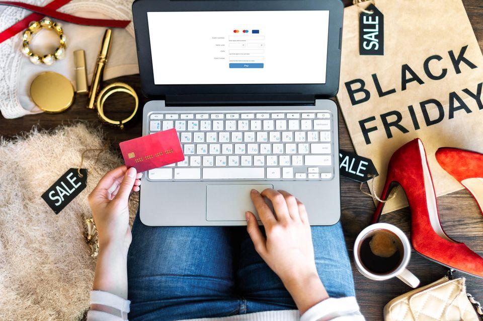Black Friday, Frau kauft online ein, hält ihre Kreditkarte fest, Schuhe, Kosmetik, Sale-Schilder liegen auf dem Boden