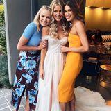 Das Brautkleid von Renae Ayris verzaubert mit seinem eleganten Off-Shoulder-Schnitt, feinstem Tüll und einem sexy Beinschlitz. Unter den Hochzeitsgästen ist unter anderem auch Erin Victoria Holland (rechts von der Braut) - sie ist eine australische Sängerin, TV-Moderatorin und Model.