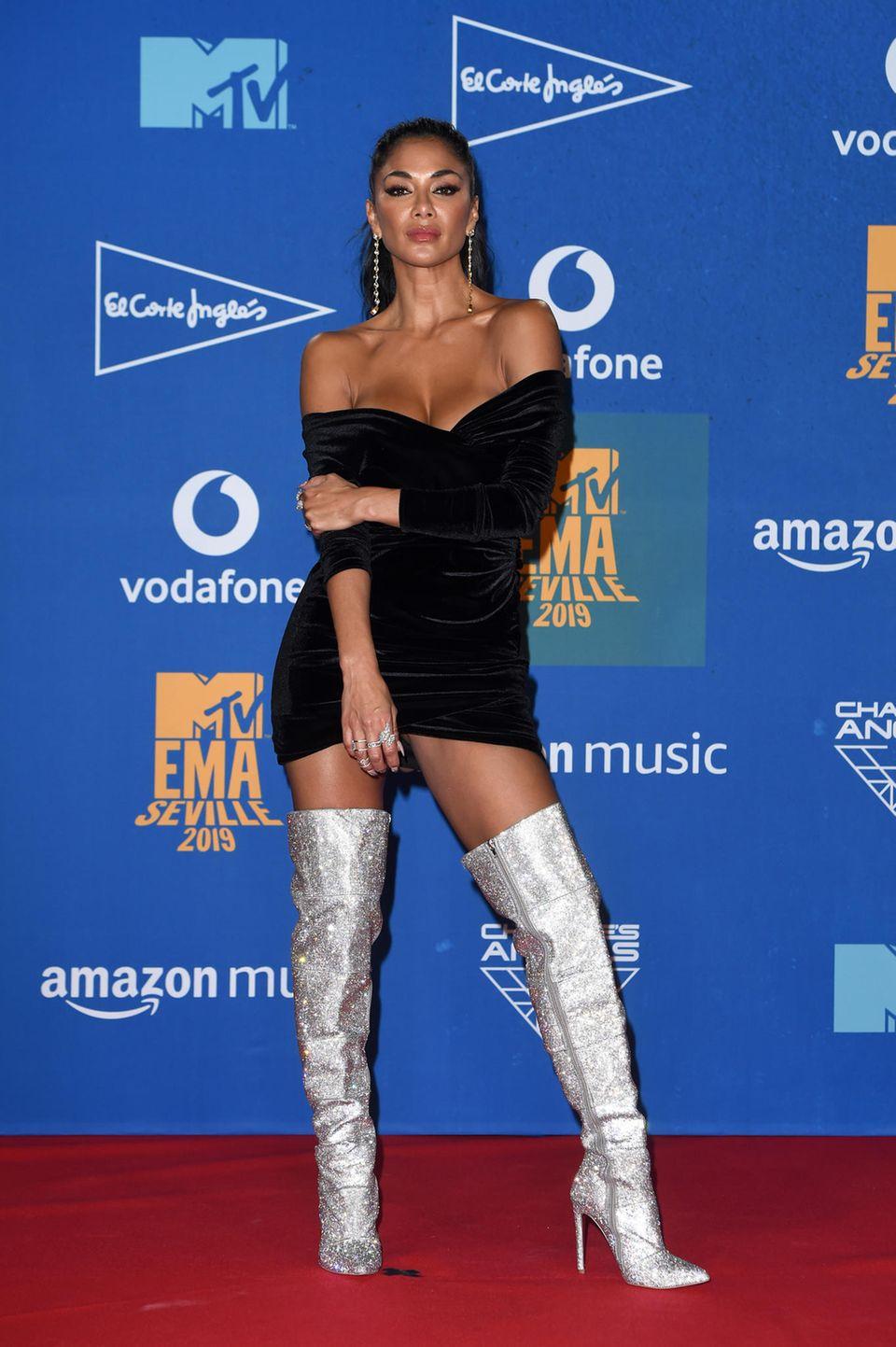 Nicole Scherzinger posiert in silbernen Overknee-Stiefeln und schwarzem Minikleid.
