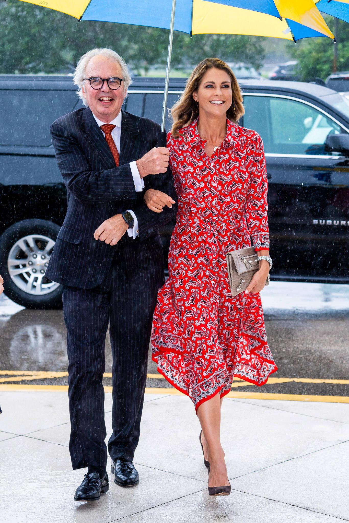 Prinzessin Madeleine strahlt trotz Regen beim zehnjährigen Jubiläum der schwedischen Kirche in Florida. Sie trägt ein Kleid mit Paisley-Muster von Veronica Beard, dazu Ohrringe von J. Crew, eine Uhr von Rolex und eine Balenciaga-Clutch.