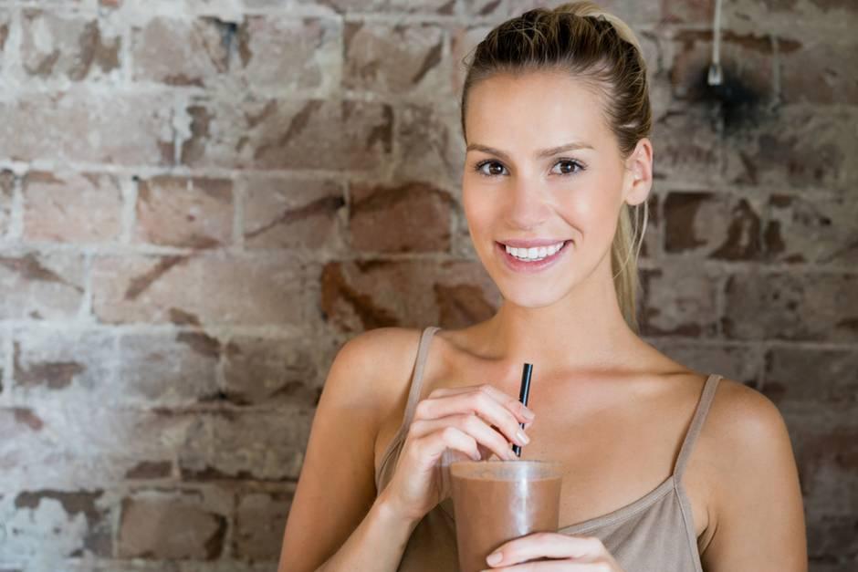 Frau mit Shake in der Hand, junge Frau hält Strohhalm von Getränk