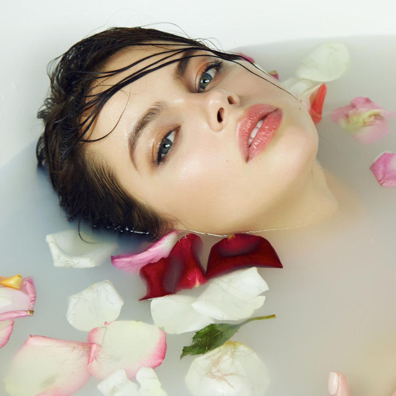 Rosenwasser, Gesicht, Frau badet in Wasser mit Rosenblättern