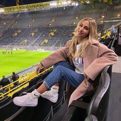 Ann-Kathrin Götze ist - genau wie Ehemann Mario - Profi! In einem stylischen und dennoch kuscheligen Look feuert sie ihn von der Tribüne an: Coole Sneaker, hohe Socken, lockere Jeans und XL-Teddy-Coat sind die perfekte Wahl für einen Nachmittag im Stadion.