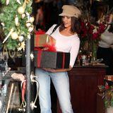 Behutsam balanciert Olivia Culpo einen Stapel mit Geschenken durch die Tür. Rote Schleifen sorgen zusätzlich für einen weihnachtlichen Look der Präsente.