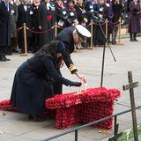 """Meghan steckt das Erinnerungskreuz in einen großen Kranz, der aus papiernen Mohnblumen geformt wurde. Die Mohnblume (im Englischen """"Poppy"""") ist das Wahrzeichen des Remembrance Day."""