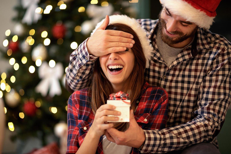 Adventskalender Paare, Frau bekommt kleines Geschenk von einem Mann überreicht, er hält ihre Augen zu