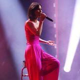 Für ihren Bühnenauftritt wählt sie dann einen roten Jumpsuit mit ausgestellten Beinen.