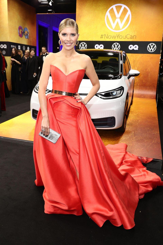 Orange und Rot gehören an diesem Abend auf jeden Fall zu den Trendfarben: Auch Victoria Swarovski setzt auf ein futuristisches Design in Signalfarbe. Streng zurückgeknotete Haare und ein goldener Gürtel machen den Look perfekt.