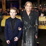 """Sharon Stone posiert mit ihrem """"man of the year"""", Sohn Roan, für die Fotografen. Das funkelnde Mantelkleid besticht durch kastige Schultern und einen großen Taillengürtel."""