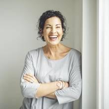lächelnde Frau lehnt an einer Wand, verschränkt die Arme