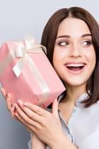 Frau mit rosa Geschenkbox in der Hand, Frau schüttelt die Box und lauscht