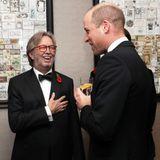 """Bei der """"London's Air Ambulance Charity Gala"""" trifft Prinz William auf Eric Clapton und hält mit ihm ein kleines Pläuschchen über die teils schlauchende Kindererziehung. Der Musiker fühlt sich sichtlich geehrt und ist auch ein wenig amüsiert."""