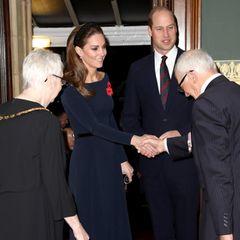"""Im Rahmen der Feierlichkeiten des """"Remembrance Day"""" in London zeigt sich die royale Familie in der Royal Albert Hall. Herzogin Kate trägt zu diesem Anlass ein dunkelblaues, tailliertes Midi-Kleid mit elegantem U-Boot-Ausschnitt, das ihre schlanke Silhouette perfekt zur Geltung bringt. Schwarze Wildleder-Pumps vonJimmy Choo und ein dazu passender Taillengürtel runden ihren Look ab. Besonderer Hingucker: Die Herzogin trägt einen funkelnden Haarreif von ZARA, der mit schwarzen Pailletten besetzt ist."""