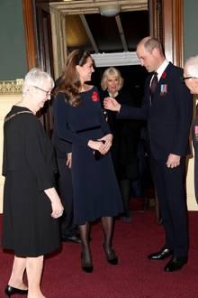 Ihr funkelnder Haarreif passt perfekt zum Rest ihres Looks: So trägt Kate ein dunkelblaues Midi-Kleid und schwarze Wildleder-Pumps von Jimmy Choo für rund 800 Euro. Einestilvolle Leder-Clutch von Alexander McQueen rundetden Style der Herzogin ab.