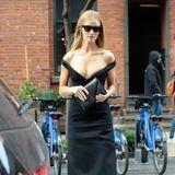 Dergroße V-Ausschnitt des Kleids und seine tief hängenden Träger machen aus einem einfachen, schwarzen Dress eine atemberaubende Robe. Rosie ist sich dieser Wirkung bewusst und trägt ihr Kleid stolz ohne jeglichen Überwurf durch die Stadt – und das trotz der dort herrschenden herbstlichen Temperaturen.