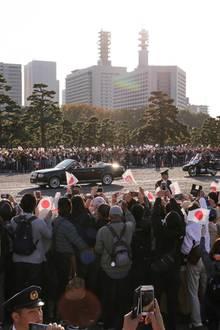 Zehntausende Menschen jubeln Kaiser Naruhito und Kaiserin Masako Fähnchen schwenkend zu.Die Fahrt in dem offenen Wagen führt vom Palast über eine knapp fünf Kilometer lange Strecke zur kaiserlichen Residenz im Stadtteil Akasaka.