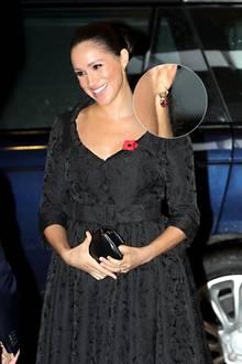 """Für das abendliche """"Festival of Remembrance"""" in der Londoner Royal Albert Hall trägt Herzogin Meghan ein Kleid von Erdem. Die streng zurückgeknoteten Haare und der Ausschnitt des maßgeschneiderten Kleides lenken die Aufmerksamkeit auf ihr strahlendes Gesicht - und ihren Schmuck: Sie trägt Ohrringe mit kleinen hängenden Herzen von der Londoner Schmuckmacherin Jessica McCormack. Für ein ähnliches Modell mit hellem Diamanten können online Besichtigungen im Atelier vereinbart werden, Kostenpunkt der Ohrringe: fast 29.000 Euro."""