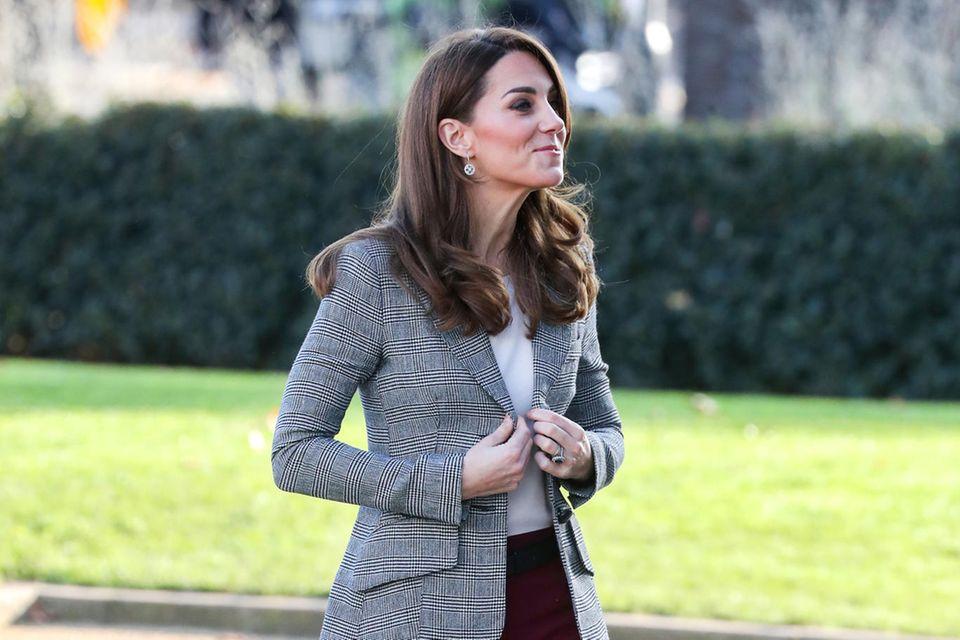 """Herzogin Catherine strahlt beiden wohltätigen """"Shout's Crisis Volunteer""""-Feierlichkeiten in London in einem herbstlichen Look: Der karierte Blazer ist von Smythe, die weinrote Hose von Joseph, dazu kombiniert Kate ein schlichtes weißes Shirt und schwarze Pumps."""